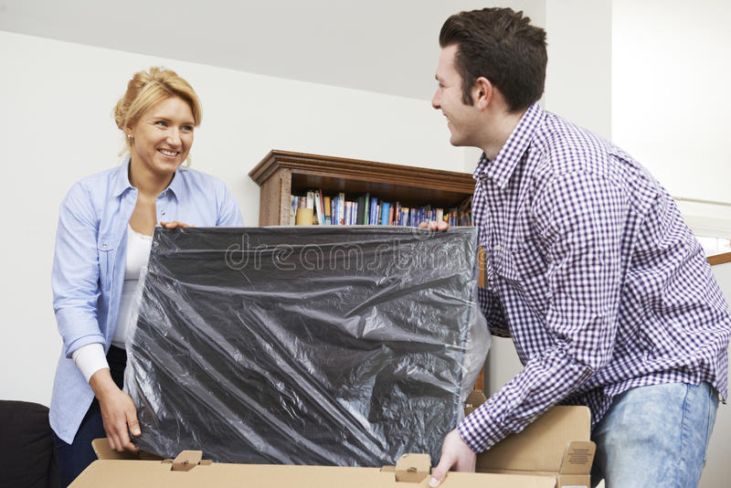 Par som hemma packar upp ny television royaltyfria foton