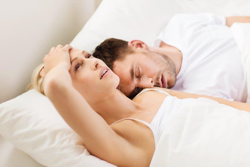 Par som hemma sover i säng fotografering för bildbyråer