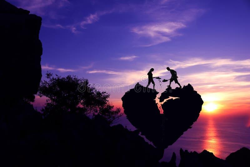 Par som hjälper till att skyffla stenen för reparation som formen för bruten hjärta vaggar på berget royaltyfri bild