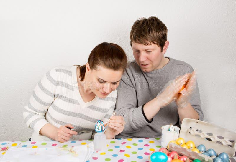 Par som inomhus dekorerar påskägg på tabellen. royaltyfri foto