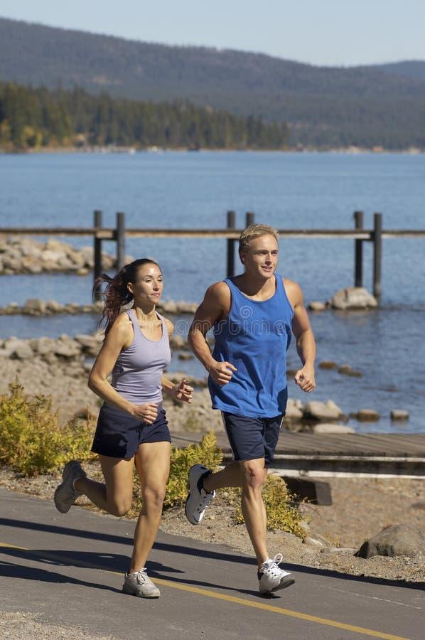 Par som joggar förbi sjön arkivbild