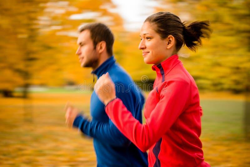 Par som joggar i naturen - rörelsesuddighet arkivbild