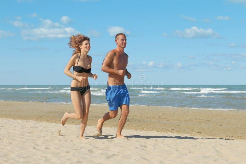 Par som joggar på stranden royaltyfri foto