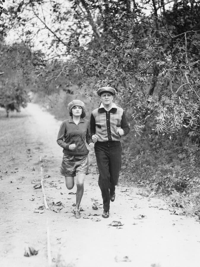 Par som joggar till och med landssidan (alla visade personer inte är längre uppehälle, och inget gods finns Leverantörgarantitha royaltyfri fotografi