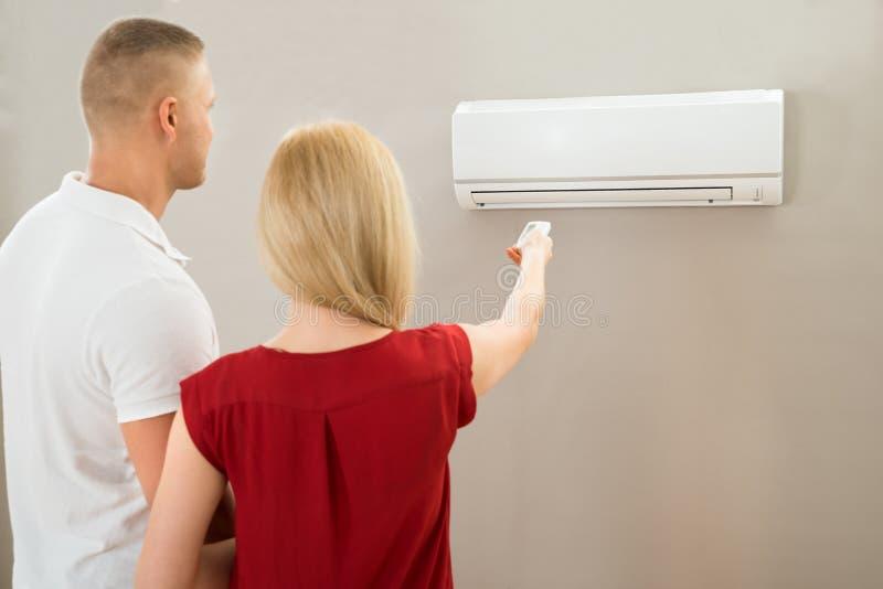 Par som justerar temperatur av luftkonditioneringsapparaten royaltyfri bild