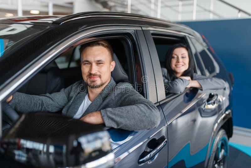 Par som köper den nya bilen, avvikelse från salongen royaltyfri fotografi