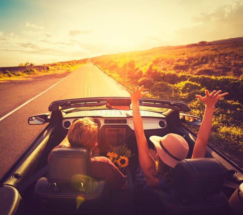 Par som kör cabrioleten på solnedgången arkivfoton