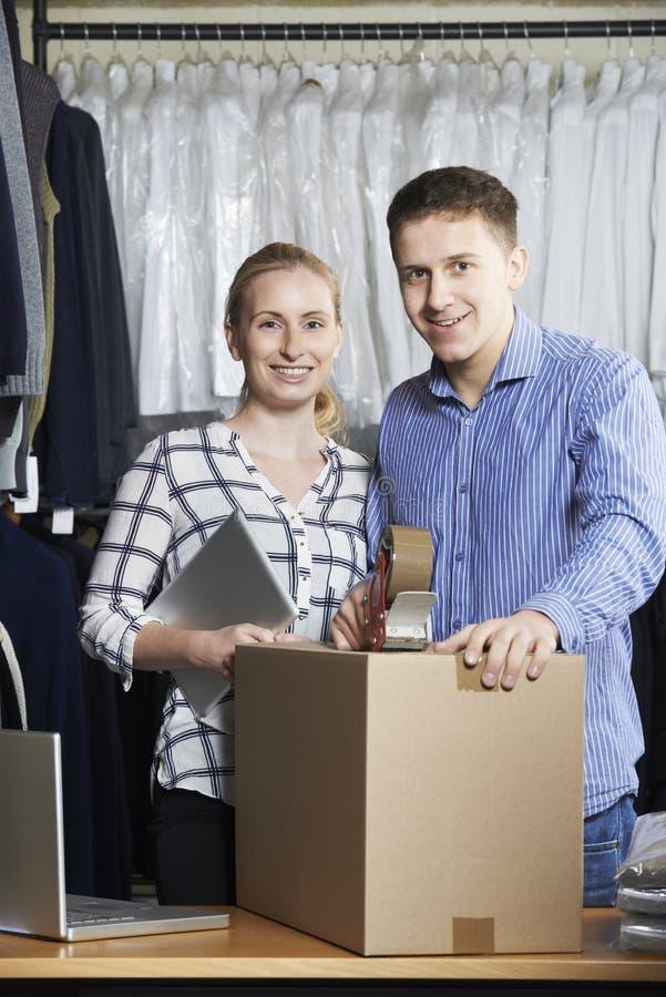 Par som kör online-gods för emballage för klädlager för utskick royaltyfri bild
