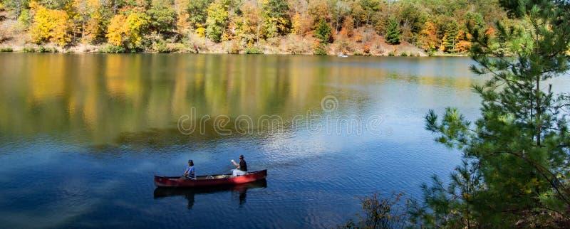 Par som kanotar på den fridsamma berg sjön arkivbilder