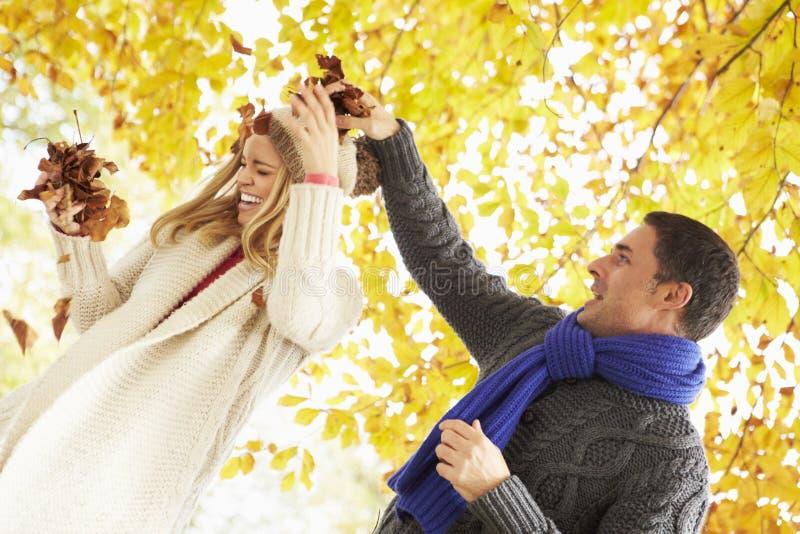 Par som kastar sidor i Autumn Garden royaltyfri bild
