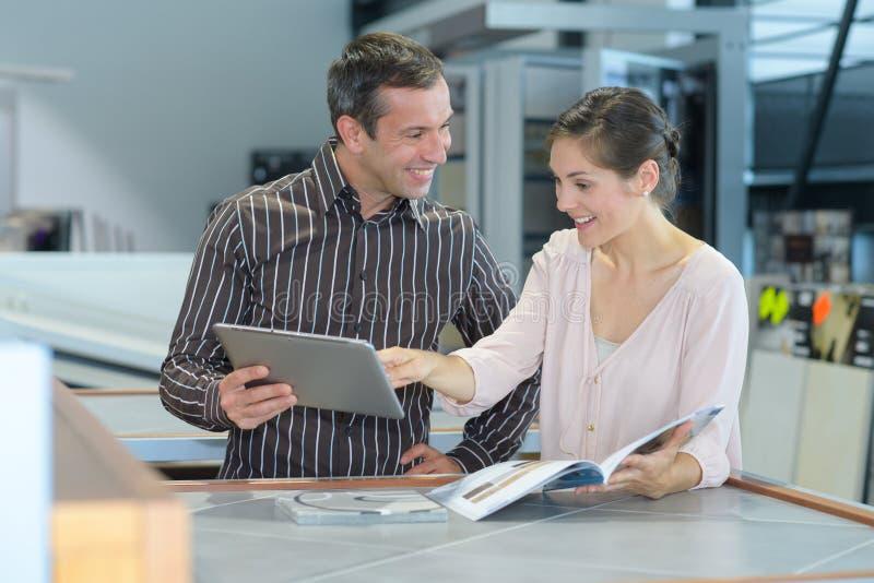 Par som kontrollerar broschyren i lager royaltyfri foto