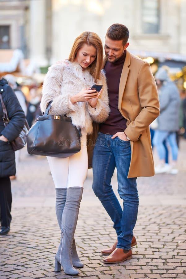Par som kontrollerar telefonen i jul, marknadsför royaltyfri foto