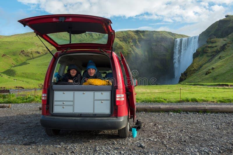 Par som kopplar av i en röd minivan, Skogafoss vattenfall i bakgrunden, Island fotografering för bildbyråer