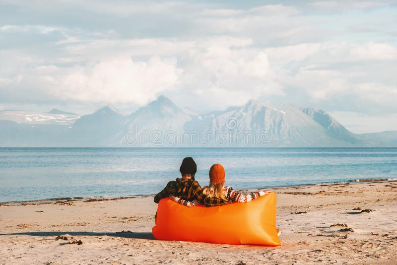 Par som kopplar av i luftdagdrivaren på stranden som tycker om havs- och bergsikt royaltyfri foto