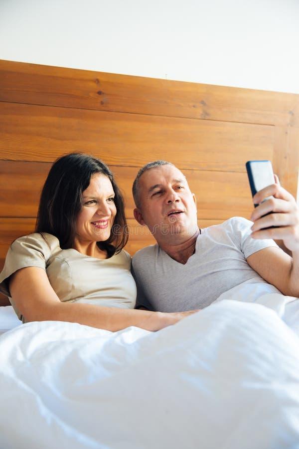 Par som kopplar av i sängen royaltyfria bilder