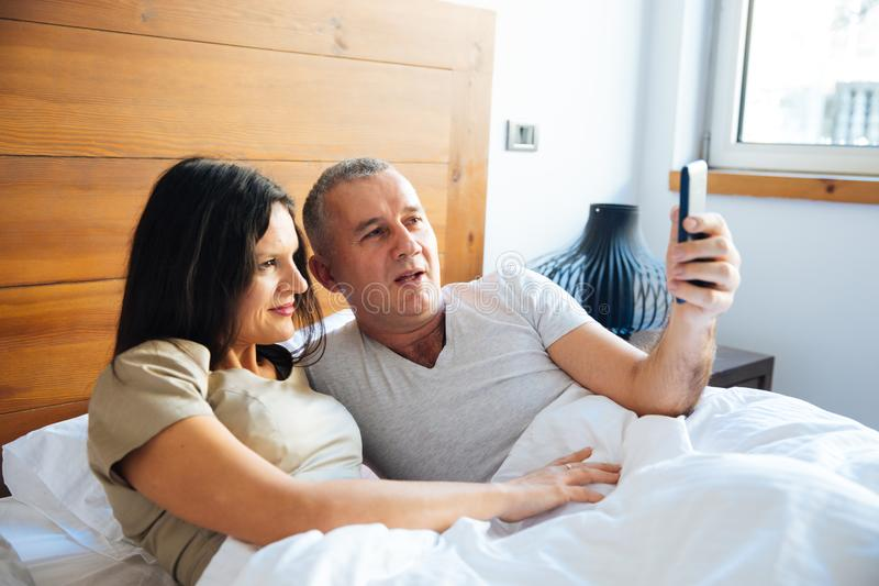 Par som kopplar av i sängen fotografering för bildbyråer