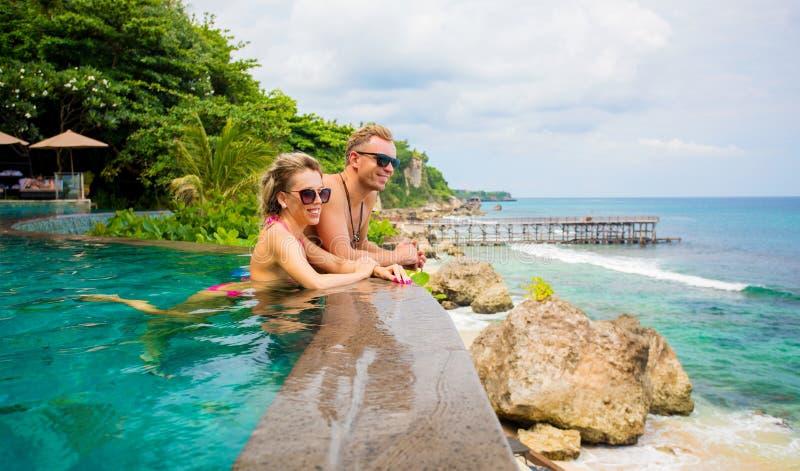Par som kopplar av i tropisk simbassäng arkivfoto