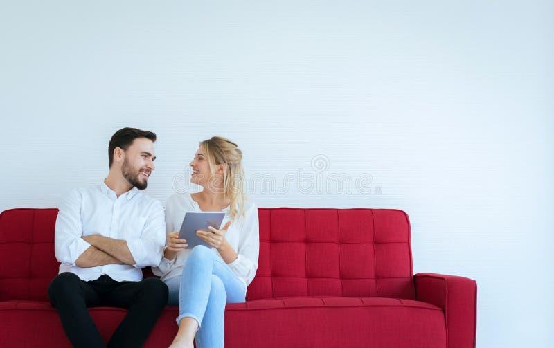 Par som kopplar av på en soffa och hemma använder minnestavlan tillsammans, lyckligt och ler, fri tid royaltyfria bilder