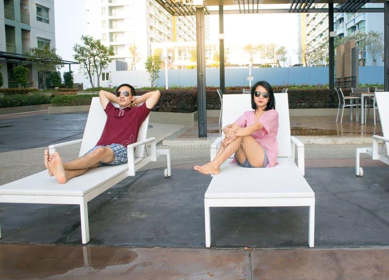 Par som kopplar av på simbassänghotellet royaltyfri bild