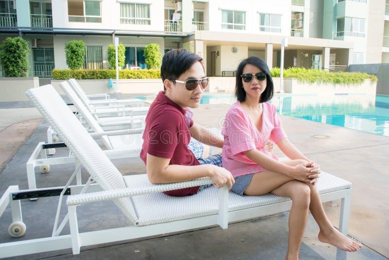Par som kopplar av på simbassänghotellet royaltyfria foton
