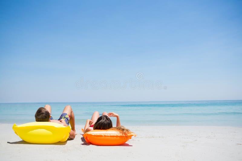 Par som kopplar av på stranden royaltyfri fotografi
