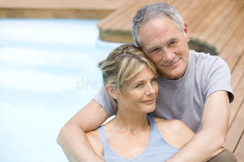 Par som kopplar av vid simbassängen arkivfoto