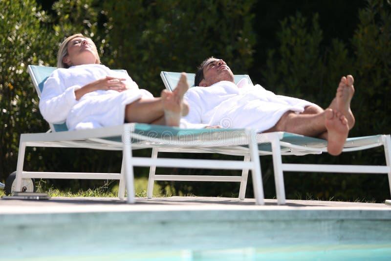 Par som kopplar av vid simbassängen royaltyfri fotografi