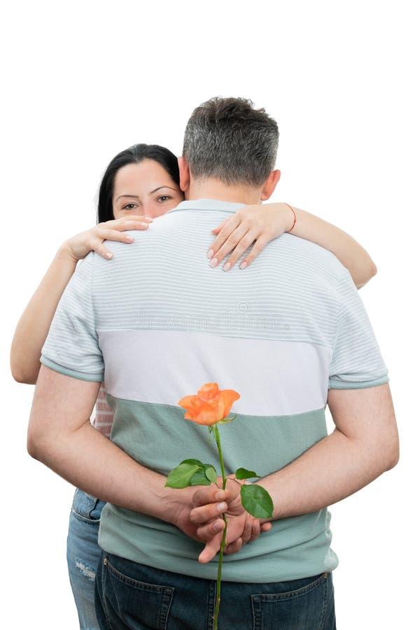 Par som kramar med mannen som döljer rosen royaltyfri bild