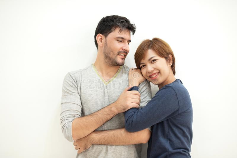Par som kramar, medan stå över den vita väggen royaltyfri fotografi