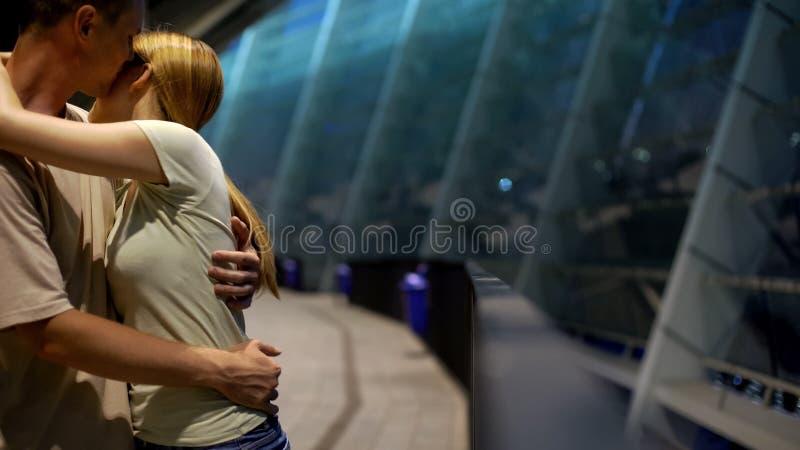 Par som kramar nära sportstadion, romantiskt datum av fotbollsfan, förhållanden arkivfoton