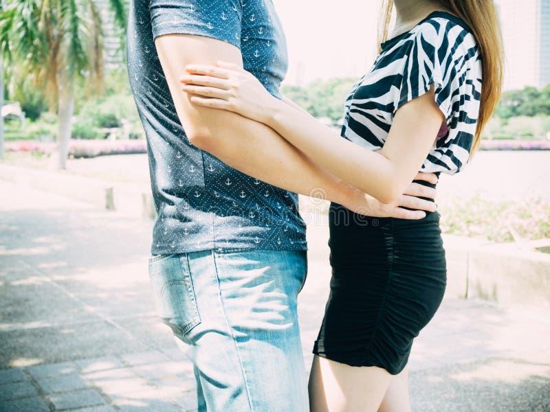 Par som kramar och kelar sig parkerar offentligt royaltyfri bild