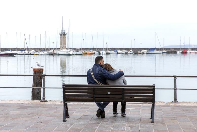 Par som kramar på en bänk Unga par som sitter på en träbänk royaltyfria bilder