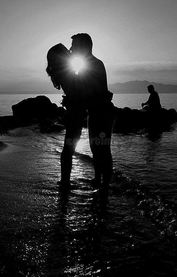 Par som kysser i havstrand på solnedgången royaltyfri fotografi