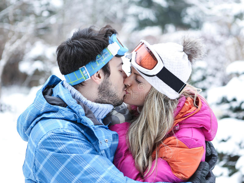 Par som kysser i vinter skidar på arkivfoton