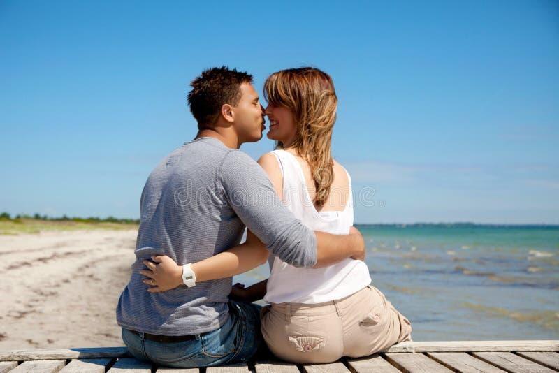 Par som kysser på en sommarstrand arkivbild