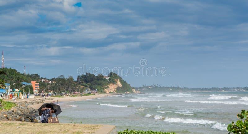 Par som kysser under paraplyet på stranden royaltyfri foto