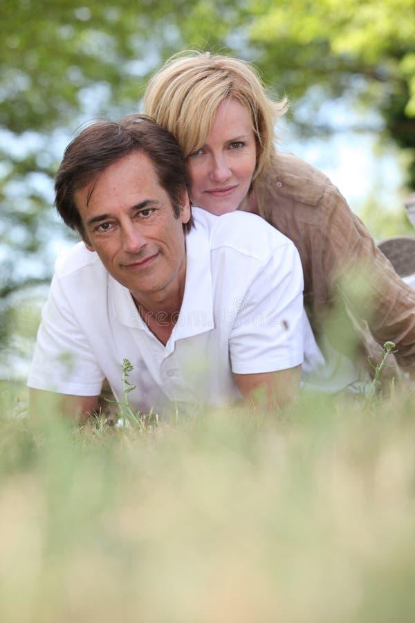 Par som lägger i ett fält fotografering för bildbyråer