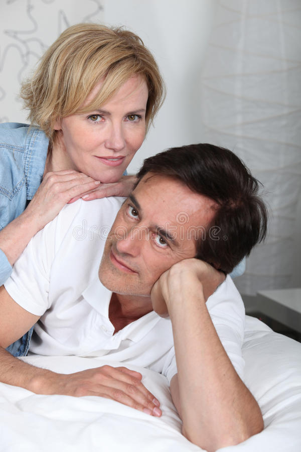 Par som lägger ner på säng royaltyfria bilder