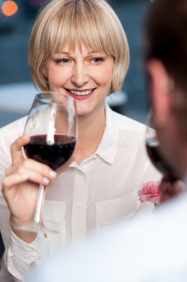 Par som läppjar rött vin och hyser minnen royaltyfria bilder