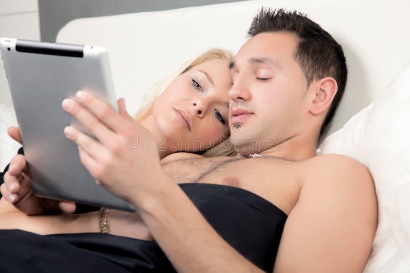 Par som läser enPC i säng royaltyfria foton
