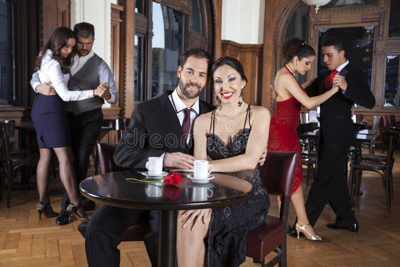 Par som ler, medan tycka om tangokapacitet i restaurang arkivbild