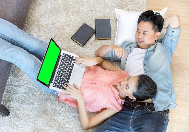 Par som ligger ner genom att använda bärbara datorn royaltyfria bilder