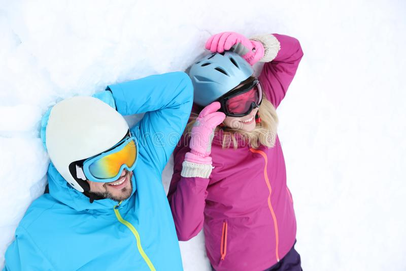 Par som ligger på snö på, skidar semesterorten Vinter royaltyfria foton