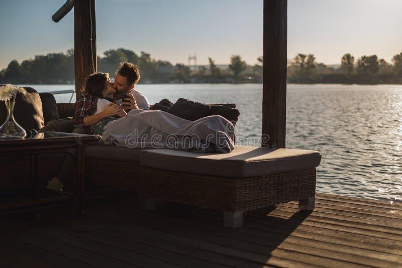 Par som ligger under filten och kysser vid floden royaltyfri bild