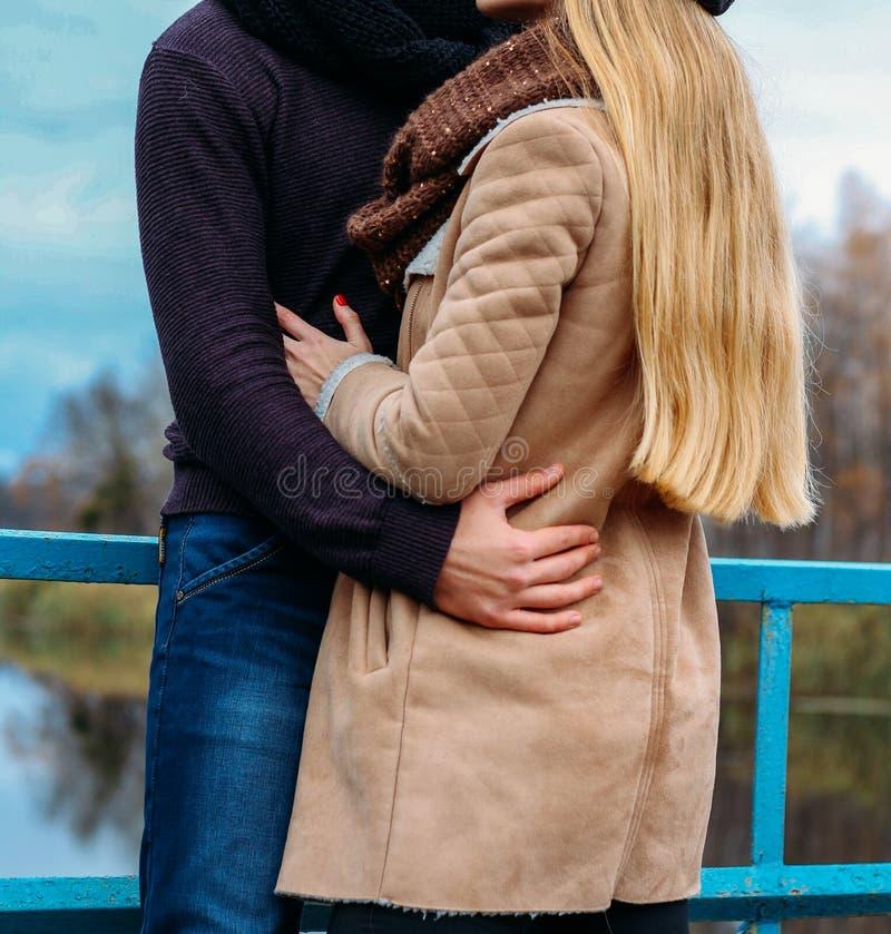Par som omfamnar på bron, nära vattnet, höst förälskelse och familjen, ett datum i parkerar vid floden arkivbild