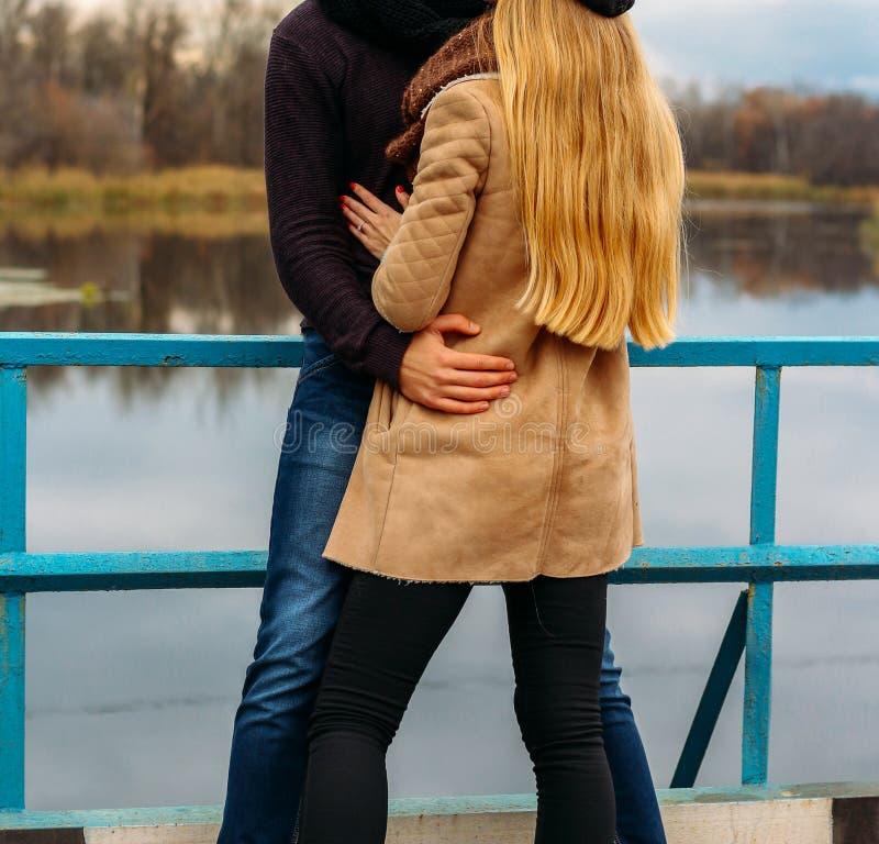 Par som omfamnar på bron, nära vattnet, höst förälskelse och familjen, ett datum i parkerar vid floden arkivbilder