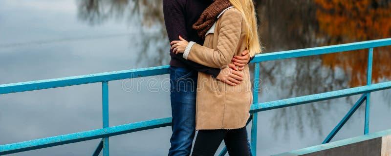 Par som omfamnar på bron, nära vattnet, höst förälskelse och familjen, ett datum i parkerar vid floden royaltyfri fotografi