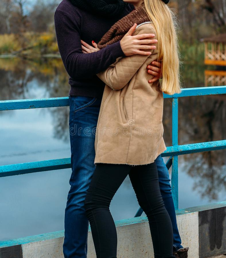Par som omfamnar på bron, nära vattnet, höst förälskelse och familjen, ett datum i parkerar vid floden royaltyfria bilder