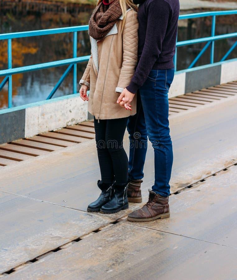 Par som omfamnar på bron, nära vattnet, höst förälskelse och familjen, ett datum i parkerar vid floden fotografering för bildbyråer