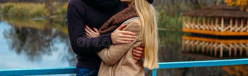 Par som omfamnar på bron, nära vattnet, höst förälskelse och familjen, ett datum i parkerar vid floden royaltyfri bild
